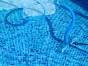 photo of vacuum hose, vac head and tele pole cleaning a pool