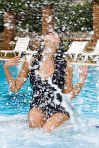 woman-splashing-water-in-a-hot-swimming-pool