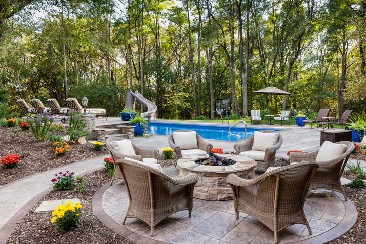 well equipped pool shown with outdoor dining set, chaise lounges and other seating areas